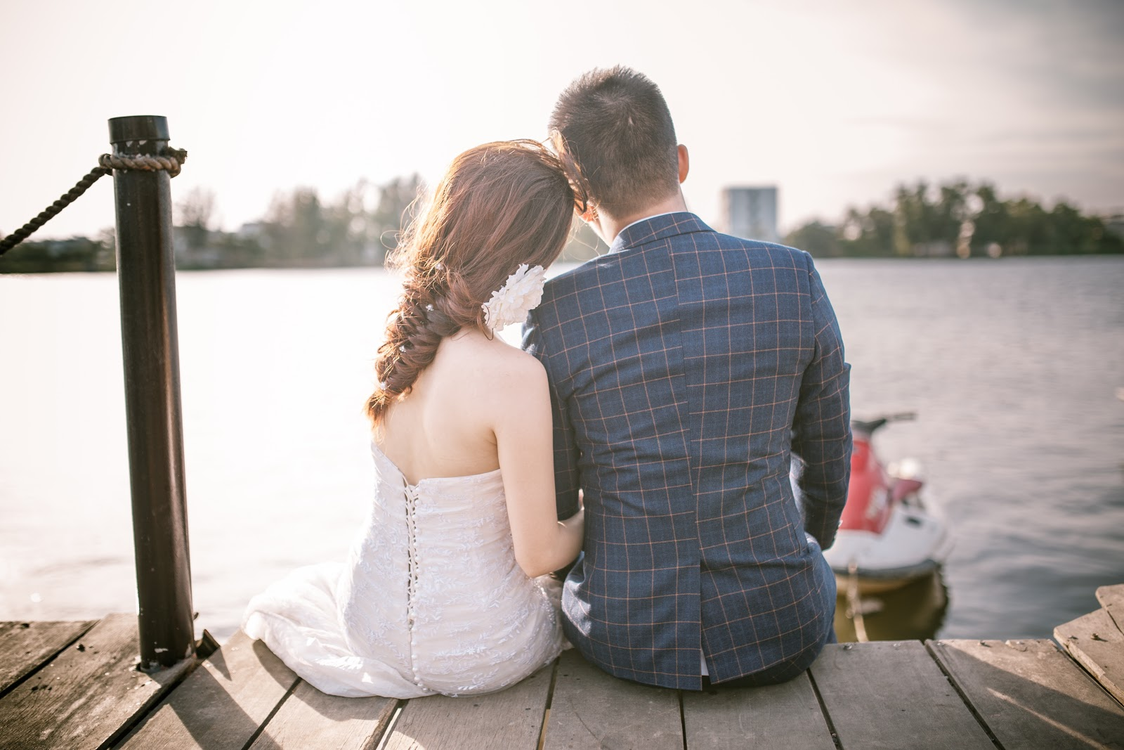wedding couple sitting on dock by water