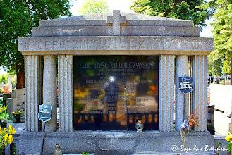 Photo: Cmentarz św. Franciszka w Łodzi. Część środkowa modernistycznego pomnika rodziny Wilczyńskich, stanowi połączenie pionowej płyty, zwieńczonej trójkątnym spłaszczonym naczółkiem i galerii kolumnowej, stworzonej przez parę potrójnych kolumn bez baz, z których środkowe mają przekrój okrągły a skrajne kanelowane - kwadratowy, dźwigające belkowanie - tworzące prześwity. Skromnego wystroju dzieła dopełnia majuskułowy napis na belkowaniu, i krzyż na osi symetrii przyczółka.