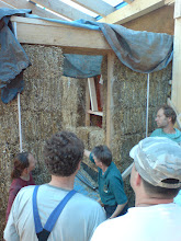 Photo: Barbara explaining about stuffing behind the door post, the curved straw edge and where the plaster edge with the hessian is to go