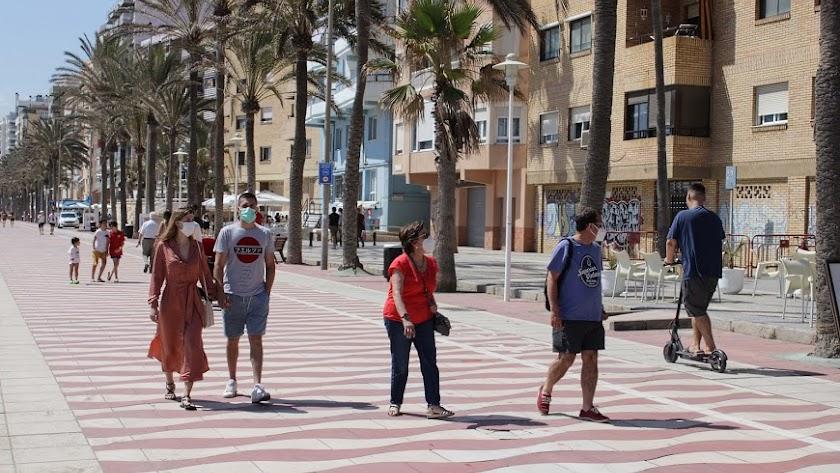 Personas con mascarilla caminando por el Paseo Marítimo de Almería.