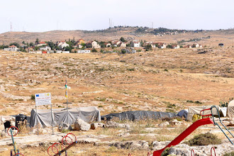Photo: After Al-Twani we visit a nearby camp of Palestinians who were expelled in 1985 out of there village Susya. They refuse to go elswhere because they stick to there land where they have there sheeep and goats. As reason for the eviction was given an archeological excavation of an ancient synagoge. In the background a Jewish settlement.