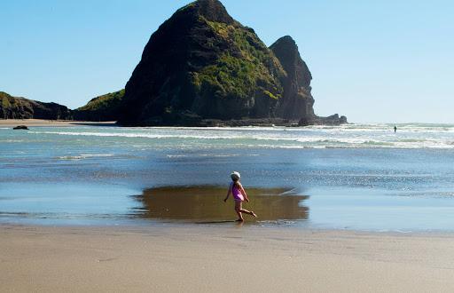 Piha-Beach-with-girl-running - A young girl runs along Piha Beach in Auckland, New Zealand.