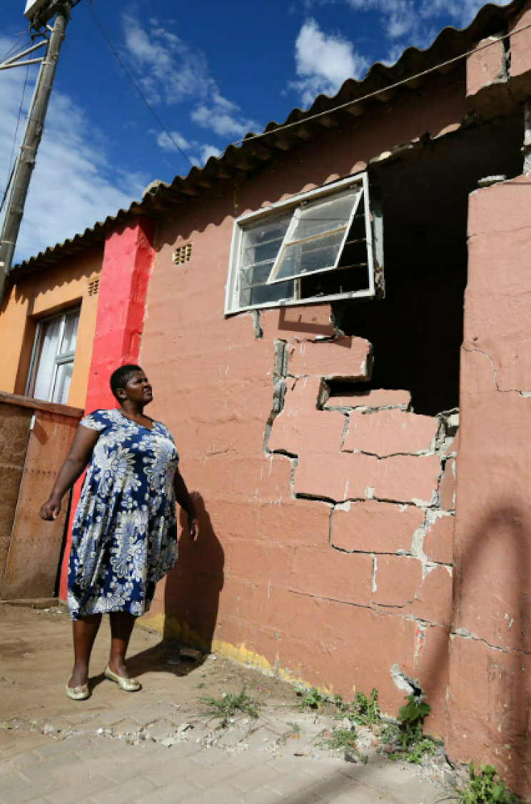 Linda Klaas surveys the damage to her Njoli Square house cause by a bus.