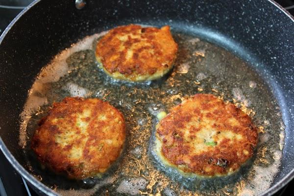 Frying tuna patties in frying pan.