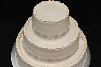 Photo: Champagne colored wedding cake w/smooth sides, tear drop borders around tops & silver diamond ribbon wrap around bottoms.