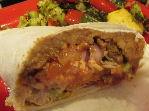 With a serrated knife cut burrito on an angle and in HALF, MAKING IT...