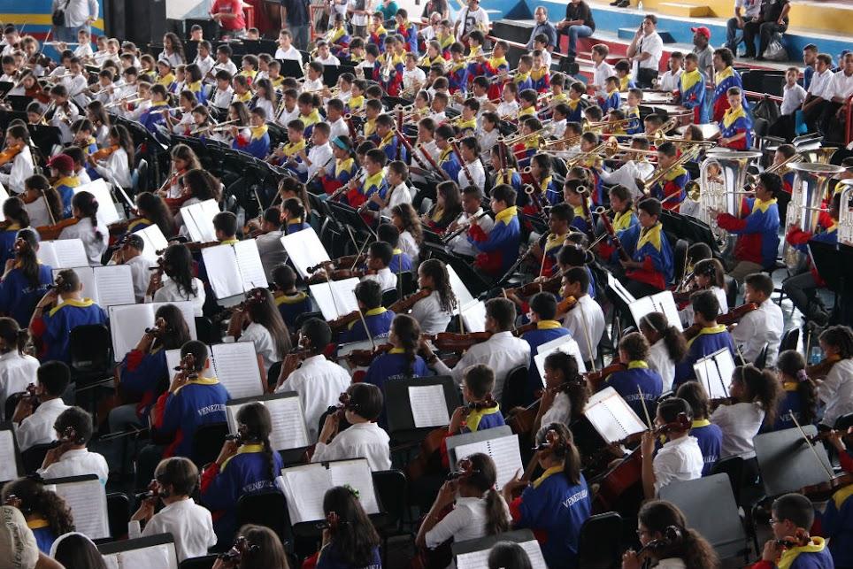 """Al unir las dos líneas de músicos de la Sinfónica Regional Infantil de Cumaná con la selección 40 Aniversario de la SNIV, la orquesta adquirió una dimensión impresionante. Los espacios del gimnasio cubierto Félix """"Lalito"""" Velásquez, retumbaron al compás del Mambo de Pérez Prado, y la habitual pieza del repertorio de las agrupaciones de El Sistema, Venezuela."""