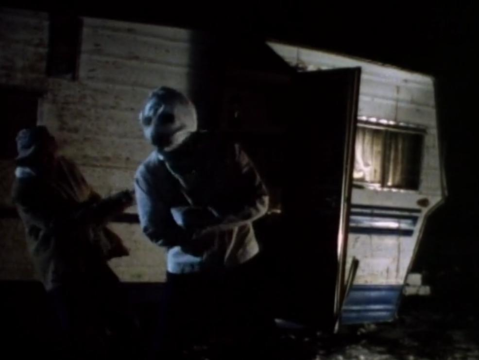 Still from Moonstalker (1989). A dark night scene: a shadowy figure lurches away from a tall figure in a straitjacket and mask that moves towards them.