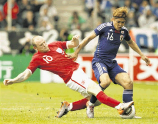 England's Wayne Rooney (L) tackles Japan's Yoshito Okubo during their international friendly soccer match in Graz, May 30, 2010.   REUTERS/Darren Staples   (AUSTRIA - Tags: SPORT SOCCER WORLD CUP)