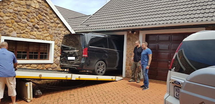 Police and private inspectors remove a black van from the garage of a house in Assagay, west of Durban, on Wednesday. The vehicle is alleged to have been used in the abduction and murder of 20-year-old Siam Lee.