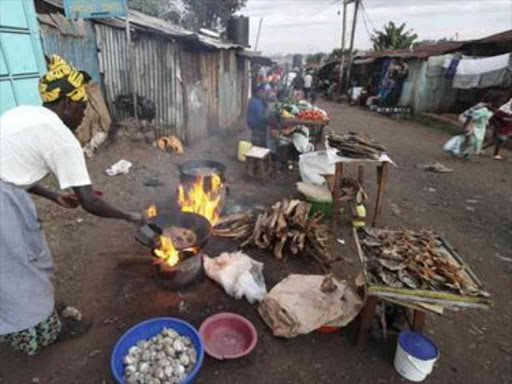 A woman fries fish along a street in the sprawling Kibera slums in Kenya's capital Nairobi April 23, 2010