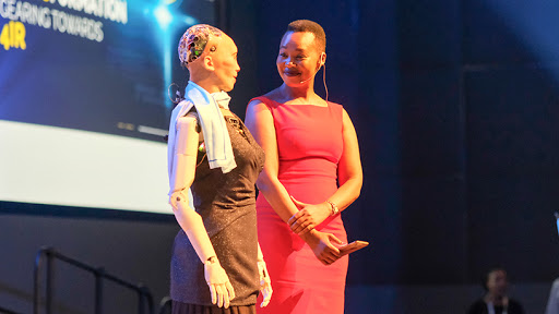 Minister Stella Ndabeni-Abrahams stands side-by-side with Sophia, the humanoid robot, at GovTech 2019.