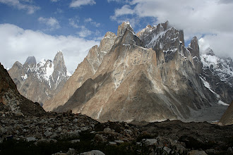 Photo: The Trango Group above the Baltoro Glacier. The high summit in cloud is Great Trango (6286m), the east face of which (on the right) is the tallest vertical rock face in the world. The Trango Tower or Nameless Tower (6239m) can be seen on the right. The peak to the left is the Uli Biaho Tower (6109m).