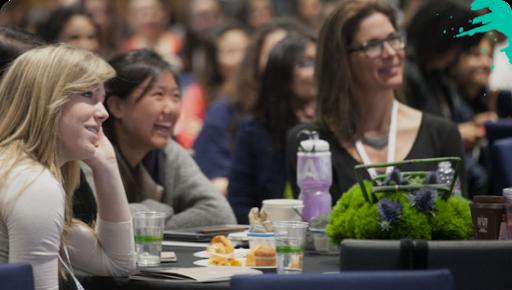 Mujeres sentadas juntas en una conferencia sobre trabajos en el sector de la tecnología.