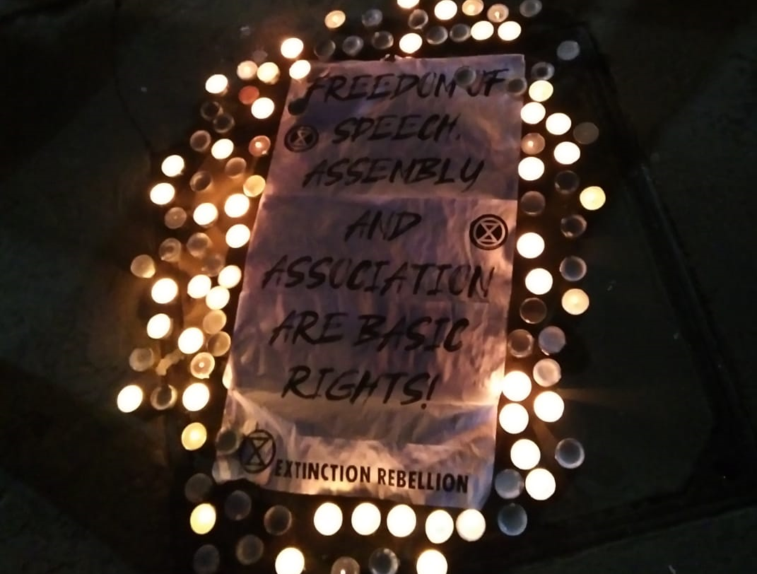 "A banner, surrounded by candles, with the text ""Freedom of Speech, Assembly, and Association are basic Rights!"""