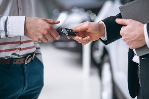 Homem passando chave de um dos melhores carros usados para outro homem.
