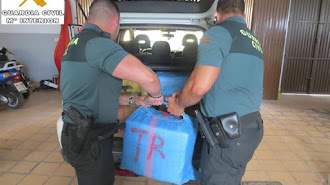 Agentes de la Guardia Civil descargan los fardos de hachís.
