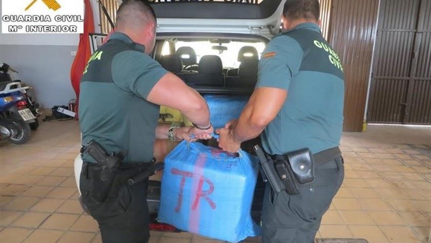 Agentes de la Guardia Civil descargan los fardos de hachís.