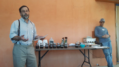 Photo: Phil Small demonstrates some simple biochar characterization methods. The row of jars on the table is a set of different biochars with equal weights of water added. As the biochar settles, the free water level above the biochar is an indication of the water holding capacity of the biochar.