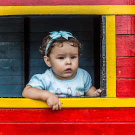 Baby Girl Through a window by Jorge A Bohorquez S - Babies & Children Babies ( red, beautiful, baby girl, face, expression, beauty, green eyes, yellow, looking, window, looking at camera, frame )