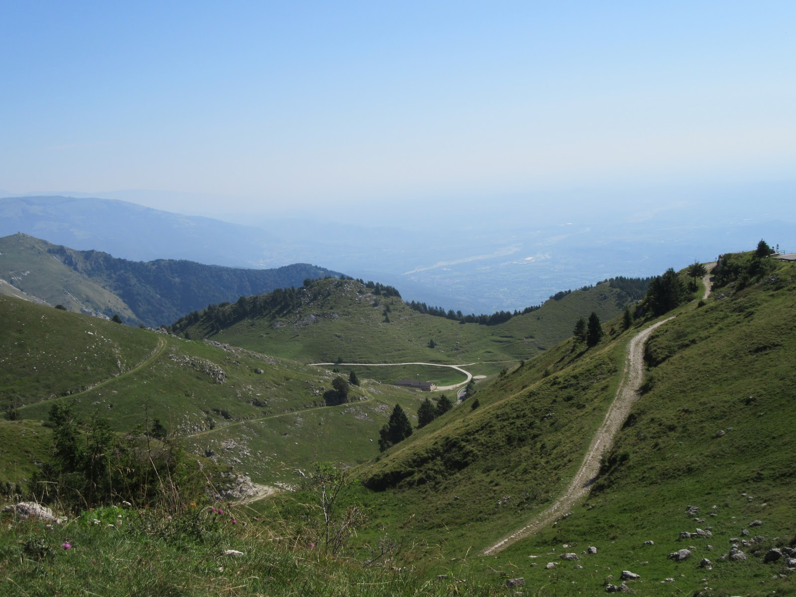 Bike climb of Monte Grappa from Crespano - gravel roadway and city below