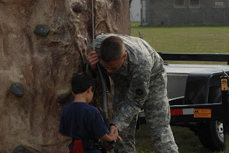 Photo: Pfc. Mark Lundequam helps a child put on his harness for rock climbing.