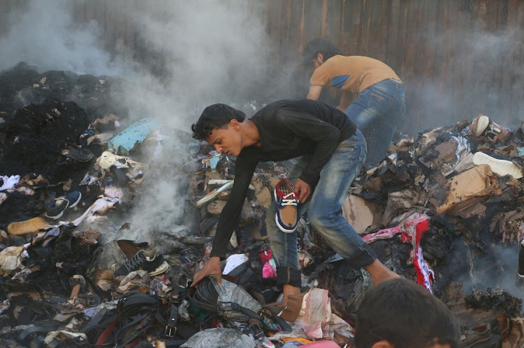 People salvage goods from an aid convoy that was damaged during an airstrike in the rebel held area of al-Sakhour district of Aleppo, Syria. File photo: REUTERS/ABDALRHMAN ISMAIL