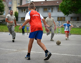 Photo: U.S. Air Force Airmen play soccer with Croatian students at an elementary school in Ogulin, Croatia, June 24, 2014. The school bathrooms are being renovated by Airmen from the 133rd and 148th Civil Engineering Squadron, and 219th RED HORSE Squadron in partnership with the Croatian army. Croatia is a Minnesota state partner under the National Guard State Partnership Program. (U.S. Air National Guard photo by Staff Sgt. Austen Adriaens/Released)