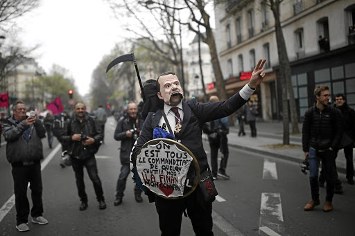 Making a statement: A demonstrator wears a mask depicting French President Emmanuel Macron at a demonstration by state-owned railway company SNCF workers in Paris on Tuesday. Picture: REUTERS