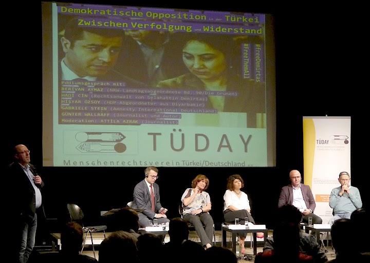 Bühne mit Diskussionsrunde, dahinter Projektion «Tüday».