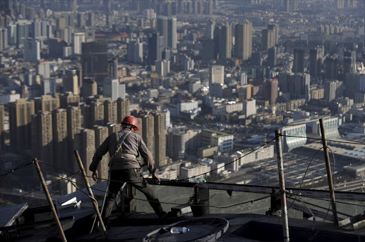 A labourer works atop a commercial building in Kunming, Yunnan province, China. Picture: REUTERS/WONG CAMPION