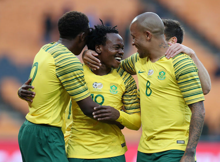 Bafana Bafana star striker Percy Tau (C) celebrates with fellow strikers Dino Ndlovu (R) and Lebo Mothiba (L) after scoring a fourth goal during the 6-0 2019 Africa Cup on Nation romp over Seychelles at FNB Stadium in Soweto, south west of Johannesburg, on October 13,2018.