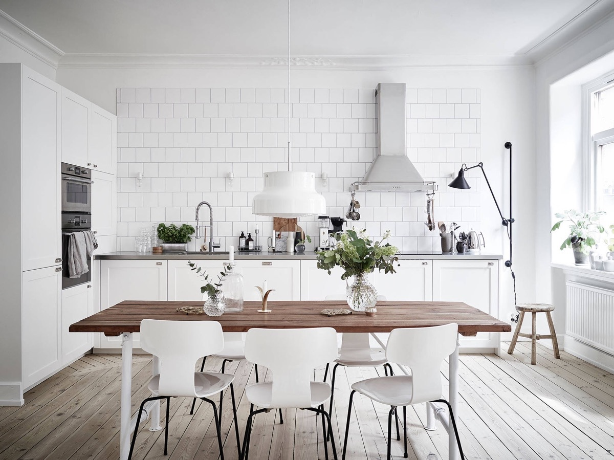 spacious white scandinavian kitchen with white subway tile backsplash, light wood floors, white furniture, white shaker cabinets and plenty of natural light