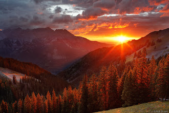 Photo: A brilliant sunset beams through the Uncompahgre River valley. The town of Ridgway is located below the sunset; Ouray would be down in the valley to the left. As seen from along the Horsethief Trail, August.