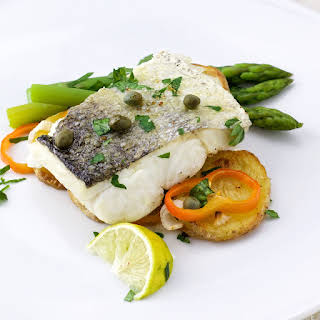 Hake Served On Roasted Potatoes And Asparagus.