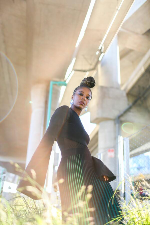foto de uma mulher negra posando com uma roupa preta e saia listrada