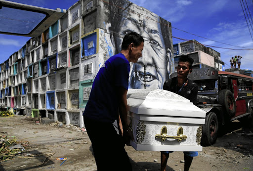 Graveyard workers carry the coffin of Eddie Languido, 56, victim of a summary execution by unknown assailants related to the Philippines' drug war, at the Navotas cemetery, north of Metro Manila, on January 31 2017. Picture: REUTERS