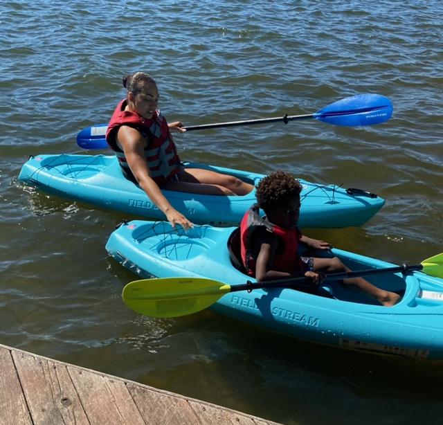 Dr. Eva helping her son kayak in the lake