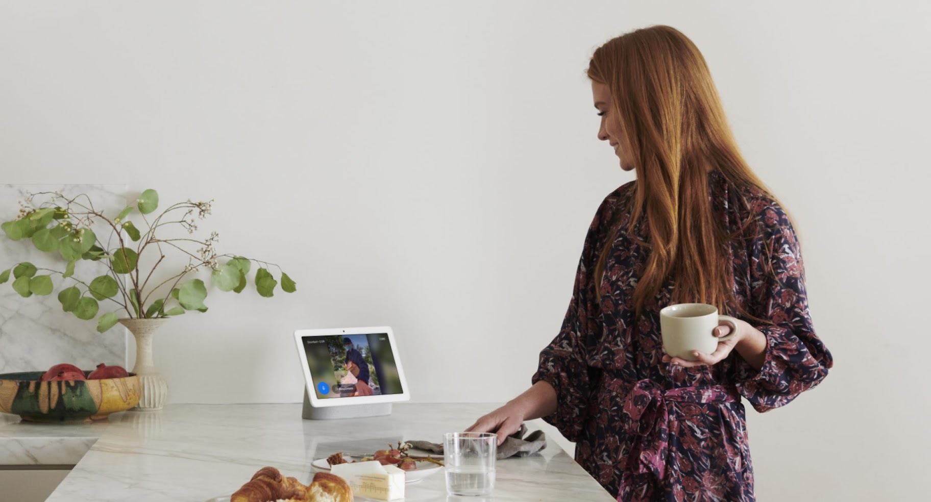 A woman drinking coffee looks at Nest Hub display on a table.