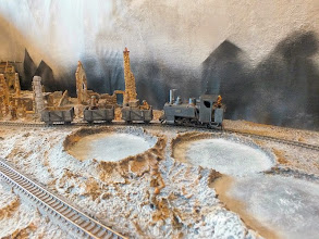 Photo: 013 A WDLR Baldwin 4-6-0T draws a train carrying stores through the shell ravaged muddy landscape of the Western Front in Matt Wildsmith's dramatic Great War scene on the Wipers, Fishhook and Menin Railway .