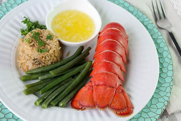 Lobster Tail On The Plate With Rice, Melted Butter, And Green Beans.