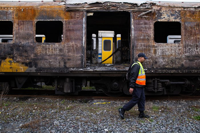 A Metrorail official walks passed a charred train carriage in Cape Town it is one of several carriages damaged in arson attacks