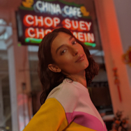 Woman in a Chinese restaurant with neon lights, smiling