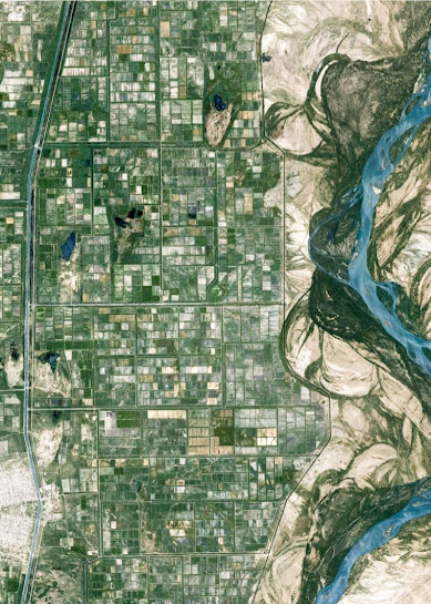 A high aerial shot of a river demarcating a city on the left and a desert on the right.