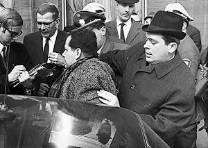 Männergruppe. Im Vordergrund: Herbert Mies wird abgeführt.