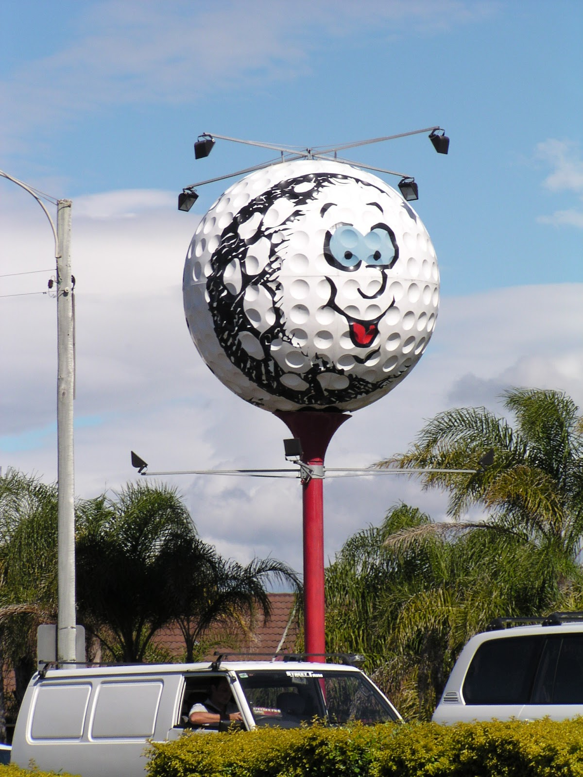 the big golf ball with a smiling face painted on it sitting on top of a pole