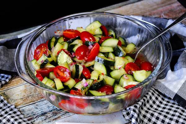 A Large Bowl Of Cucumber And Tomato Salad.