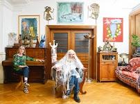 man met lange, witte, haren tot op de grond zit pontificaal in een stoel. Een vrouw zit er schuin achter op een pianokrukje