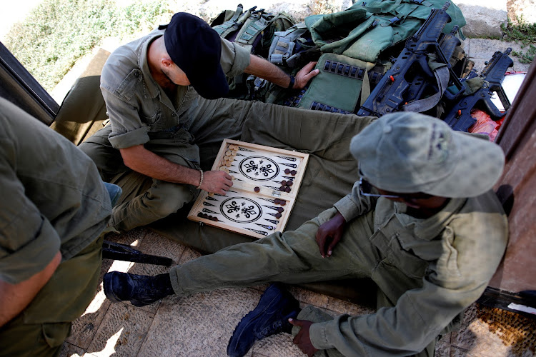 Israeli soldiers play backgammon at their post near the Israeli side of the Israel-Gaza border.
