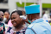 A security guard uses a thermal scanner to check a woman's temperature as she enters the Tejuoso shopping complex at the Yaba market. Nigerian health workers demanding a hazard allowance for treating coronavirus patients have called off their strike.